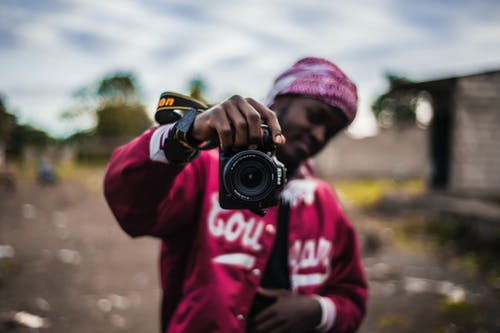 Person Holding Black Dslr Camera In Selective Focus Photography