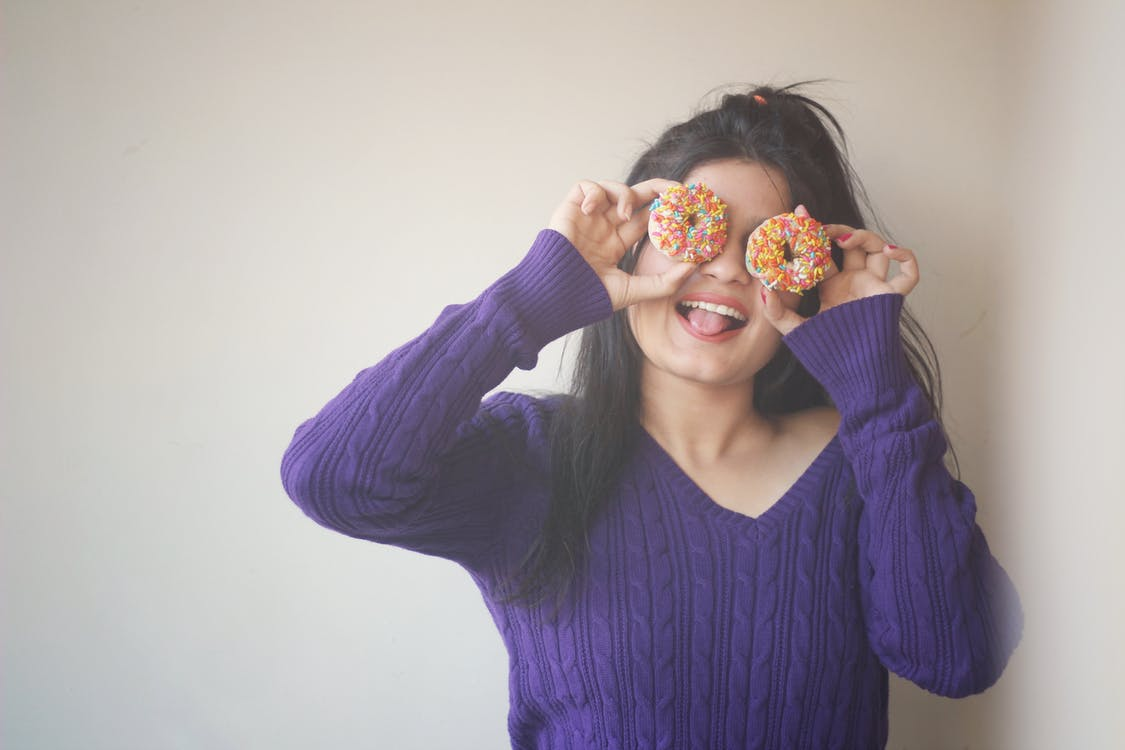 Woman Wearing Sweater Covering Her Eyes With Doughnuts