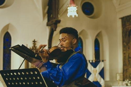 Man Playing Violin Inside Building