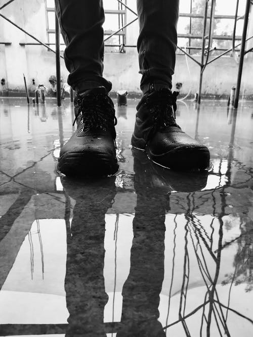 Person in Black Boots Standing on Water