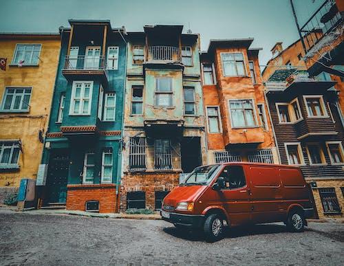 Red Van Parked Near Concrete Buildings