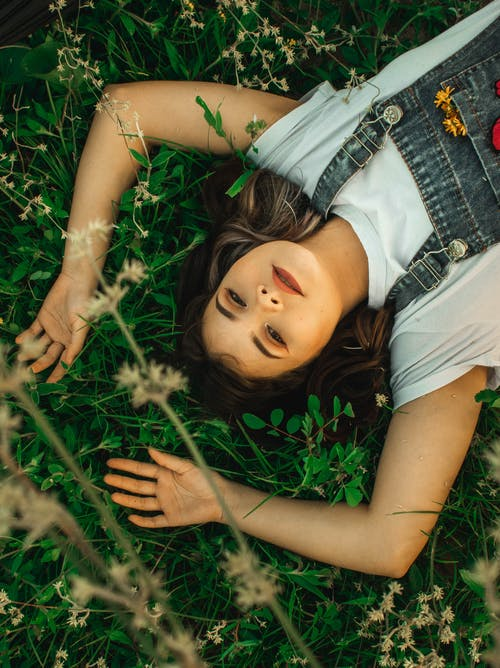 Woman Lying On Grass Field