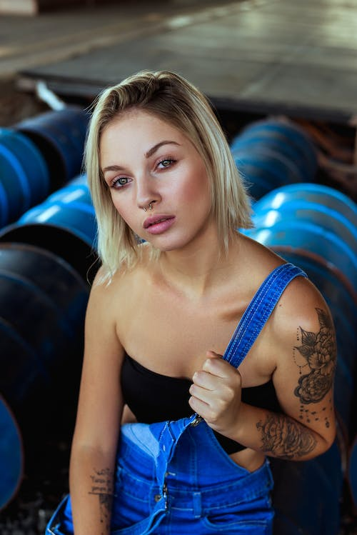Woman In Black Bandeau And Blue Denim Overalls Sitting On Barrels