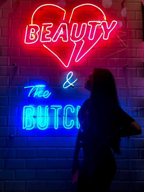 Woman Standing Near Red and Blue Neon Light Signage