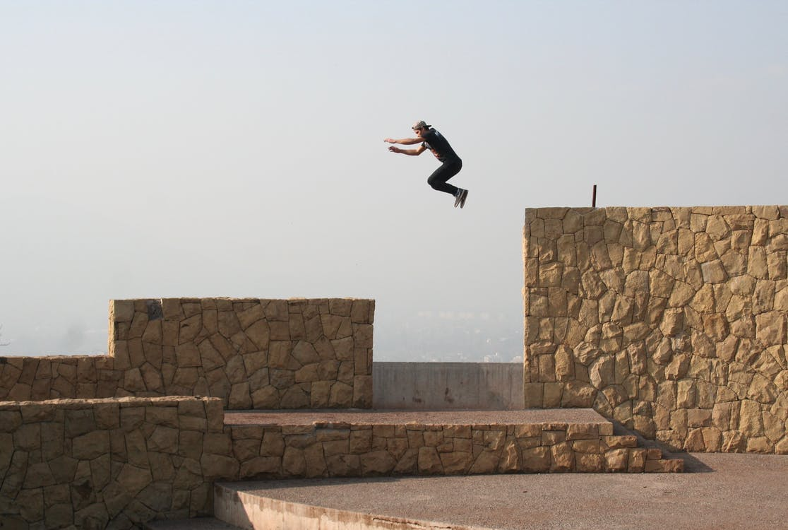 Person Jumping on Beige Concrete Wall