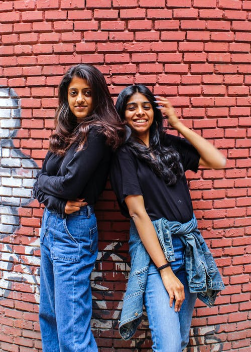 Two Woman In Black Shirts And Blue Denim Jeans
