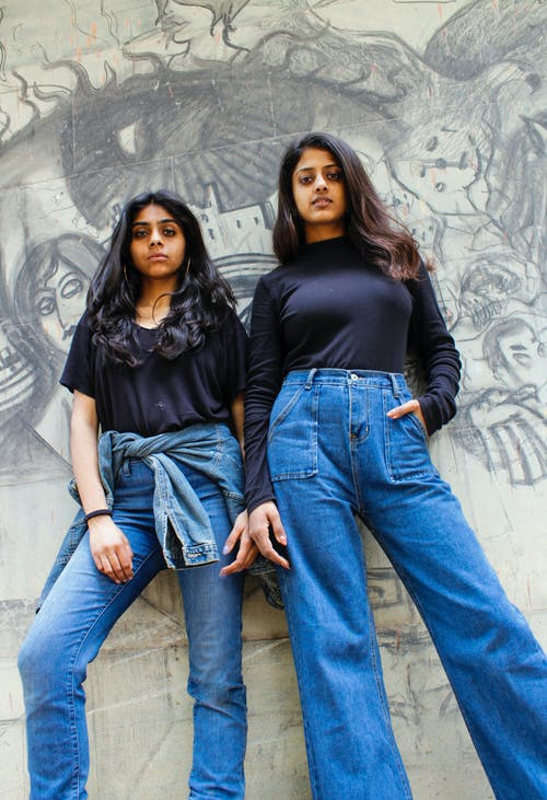 Two Women Wearing Black Tops And Blue Jeans Leaning on Concrete Wall