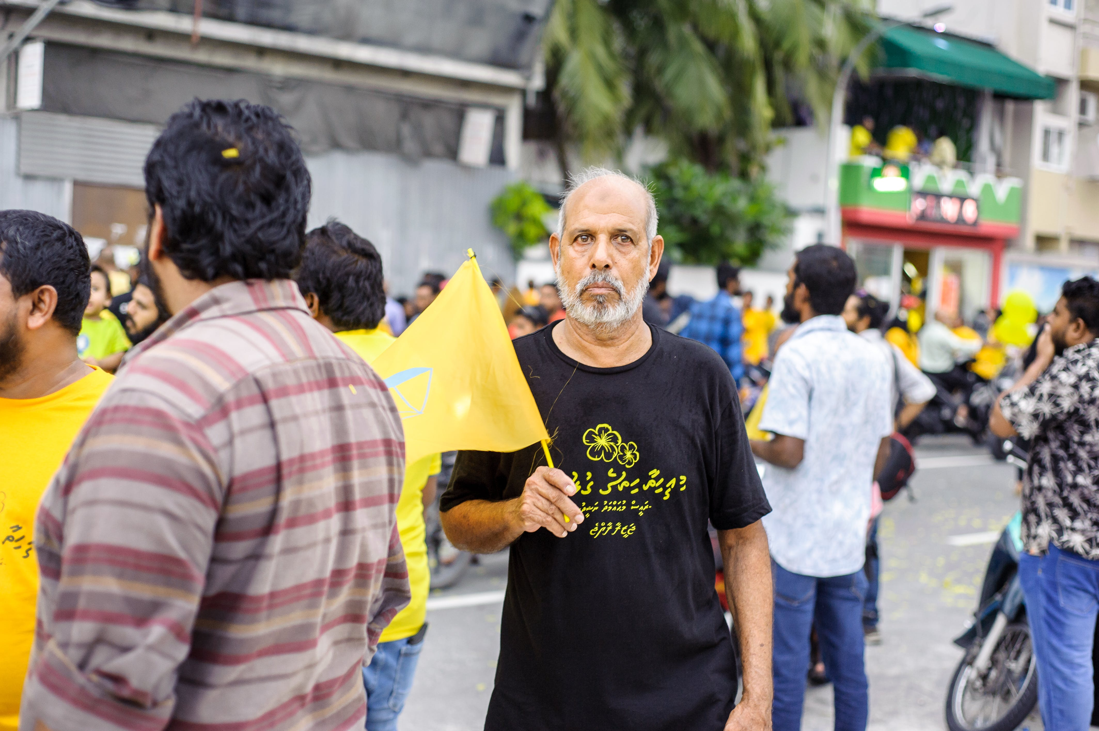 Man Standing and Holding Yellow Mini Flag