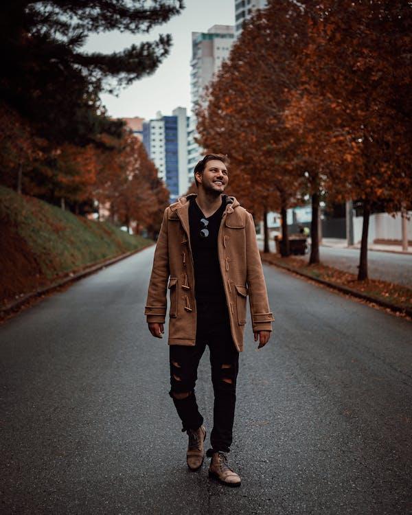 Smiling Man Walking Alone on Pathway