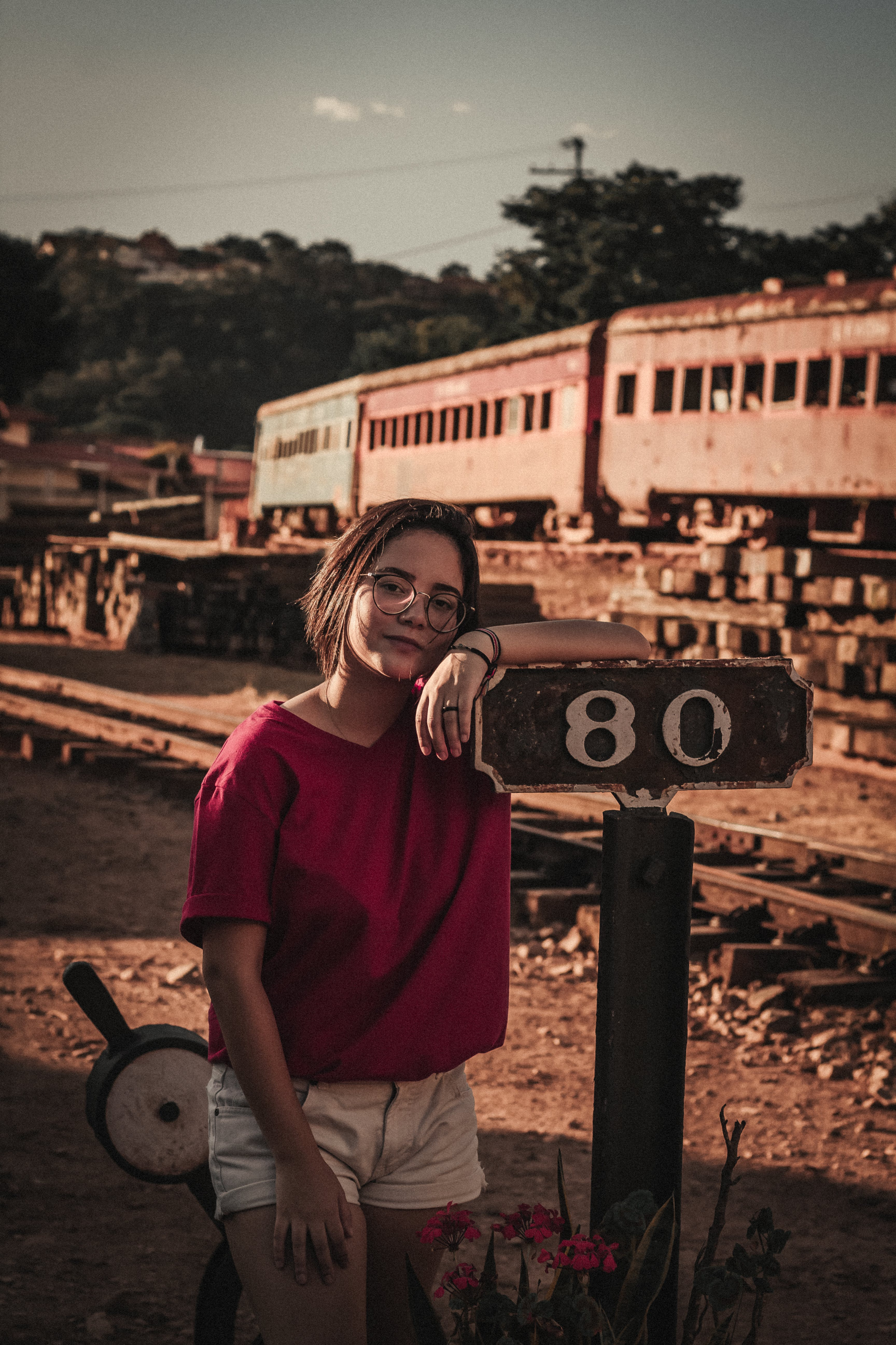 Standing Woman Wearing Red T-shirt Leaning on Brown Wooden 80 Post