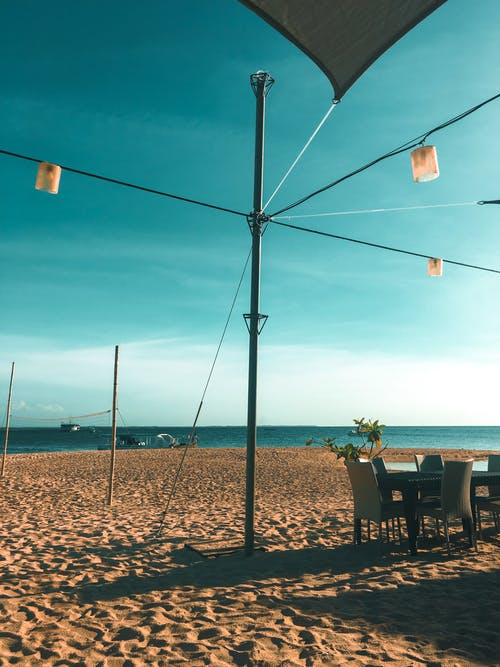 Three Pendant Lamps Near Dining Table Set Viewing Calm Sea and Seashore