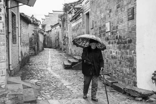 Grayscale Photography of Man Walking While Holding Umbrella