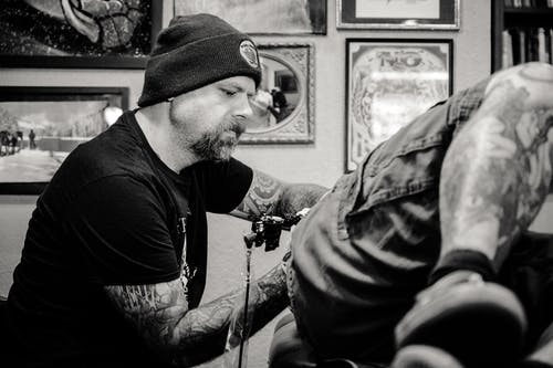 Man Tattooing Another Person
