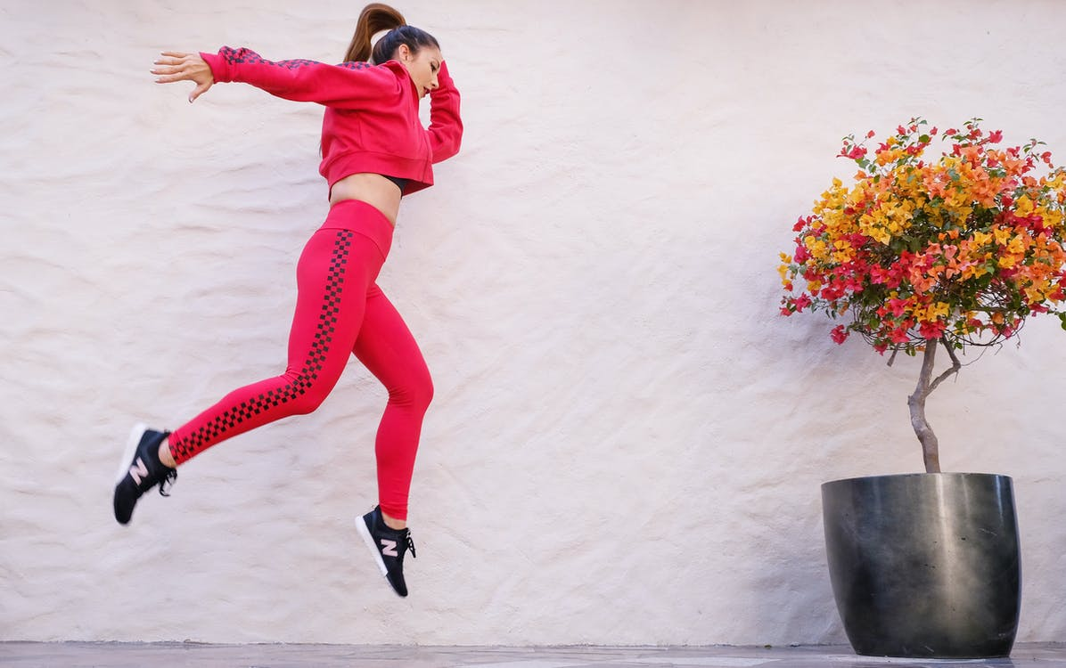 Woman in Red Tracksuit Jumping Near Wall