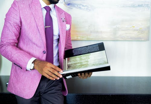 Man in Pink Suit Jacket Holding Book