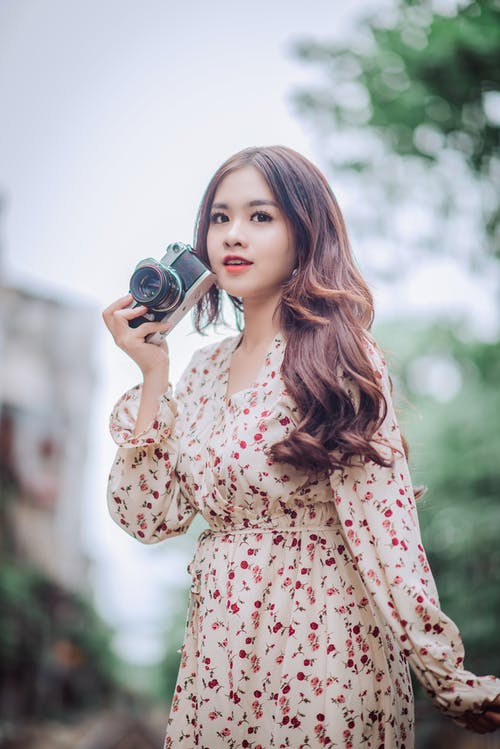 Woman in Floral Dress Holding Ccamera