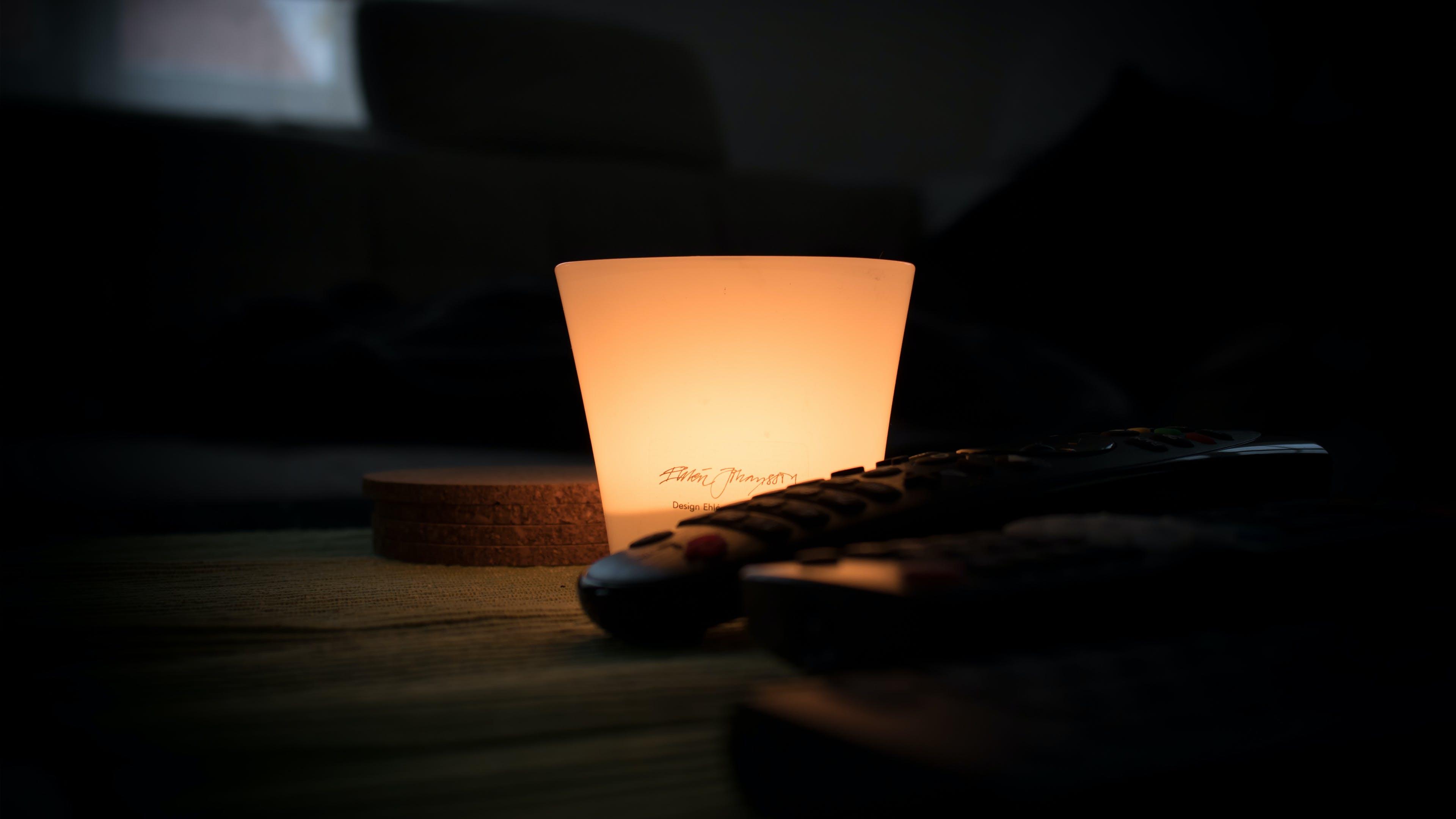 Black Remote Control Near Lamp Inside Dark Room