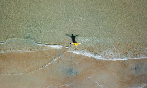 Aerial Photography of Man on Shallow Water