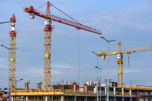 Three Yellow and Red Tower Cranes Under Clear Blue Sky