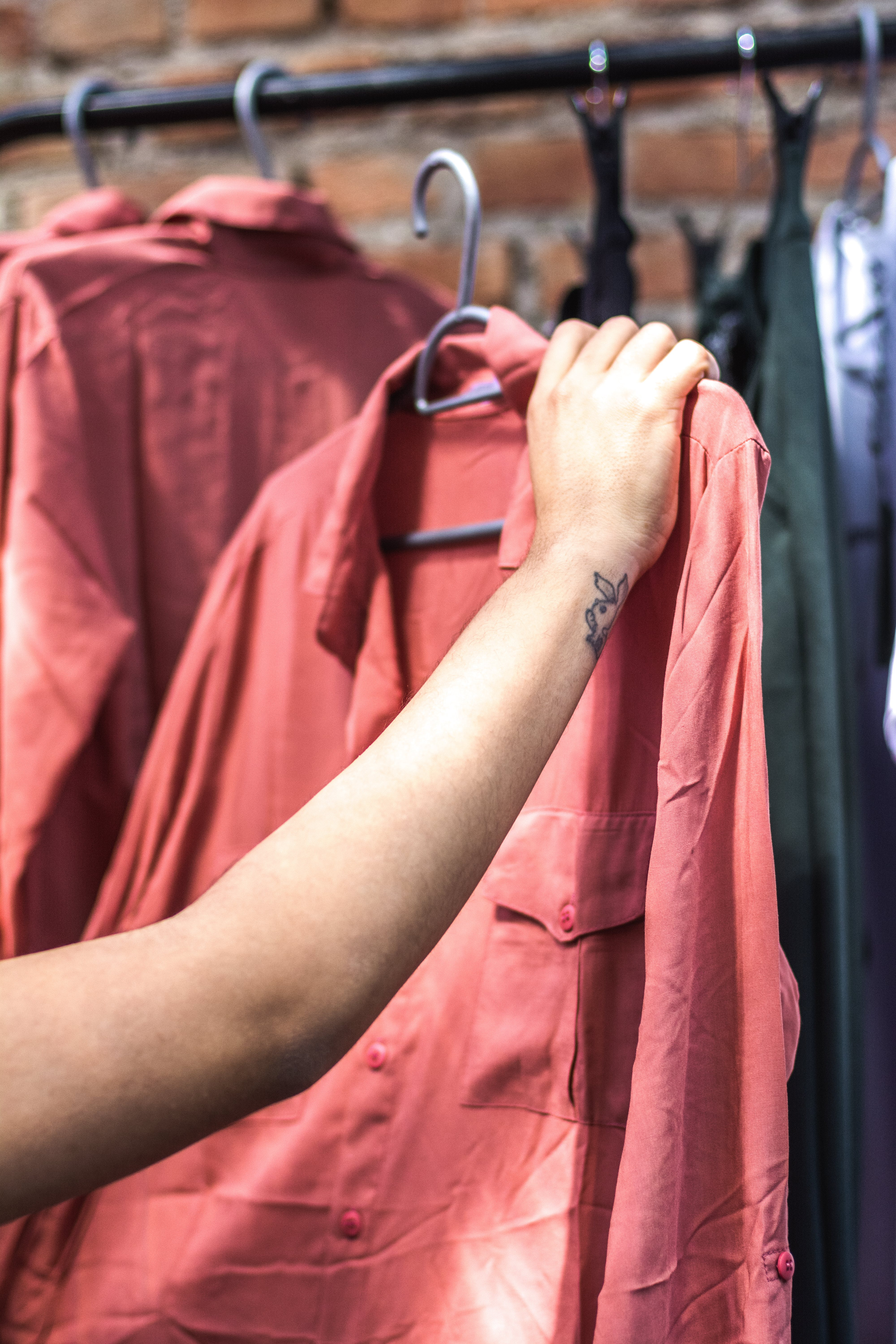 Person Holding Red Dress Shirt on Hanger