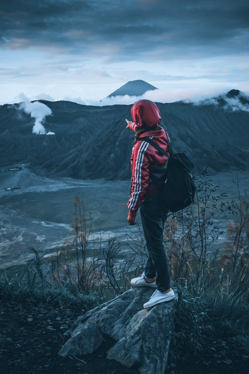 Person in Red Hoodie Standing on Rock