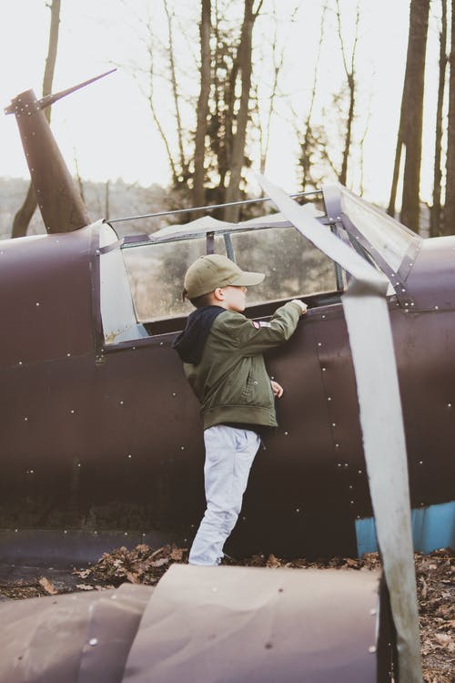 Boy Standing Beside Abandoned Plane