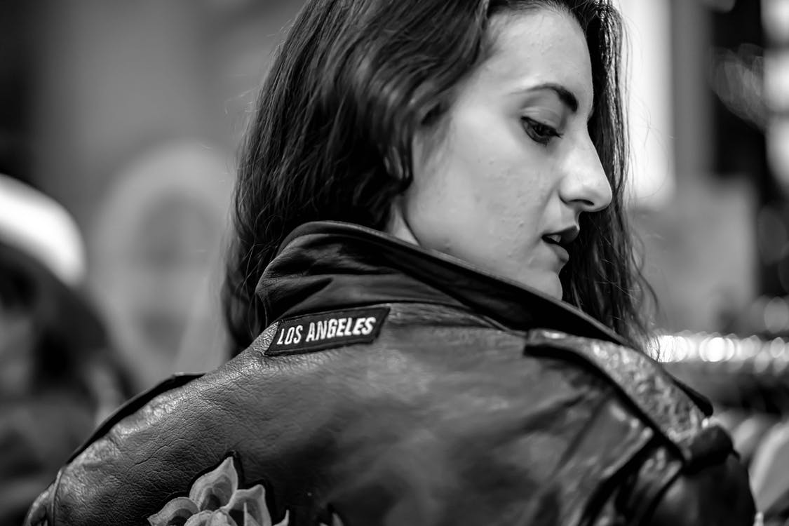Close-up Grayscale Photo of Woman in Leather Jacket Looking Back