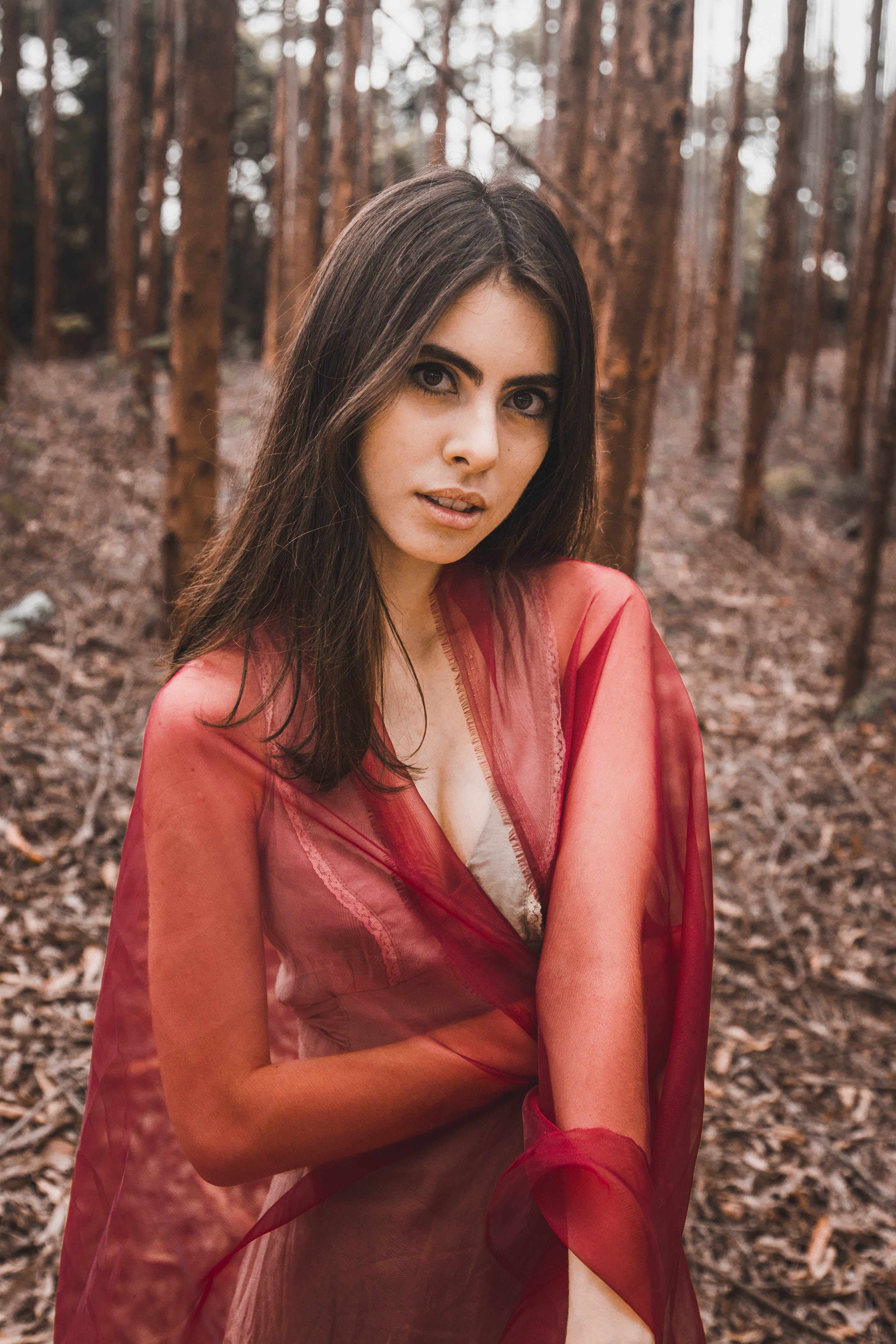 Woman Wearing Red Mesh Scarf Across Woods