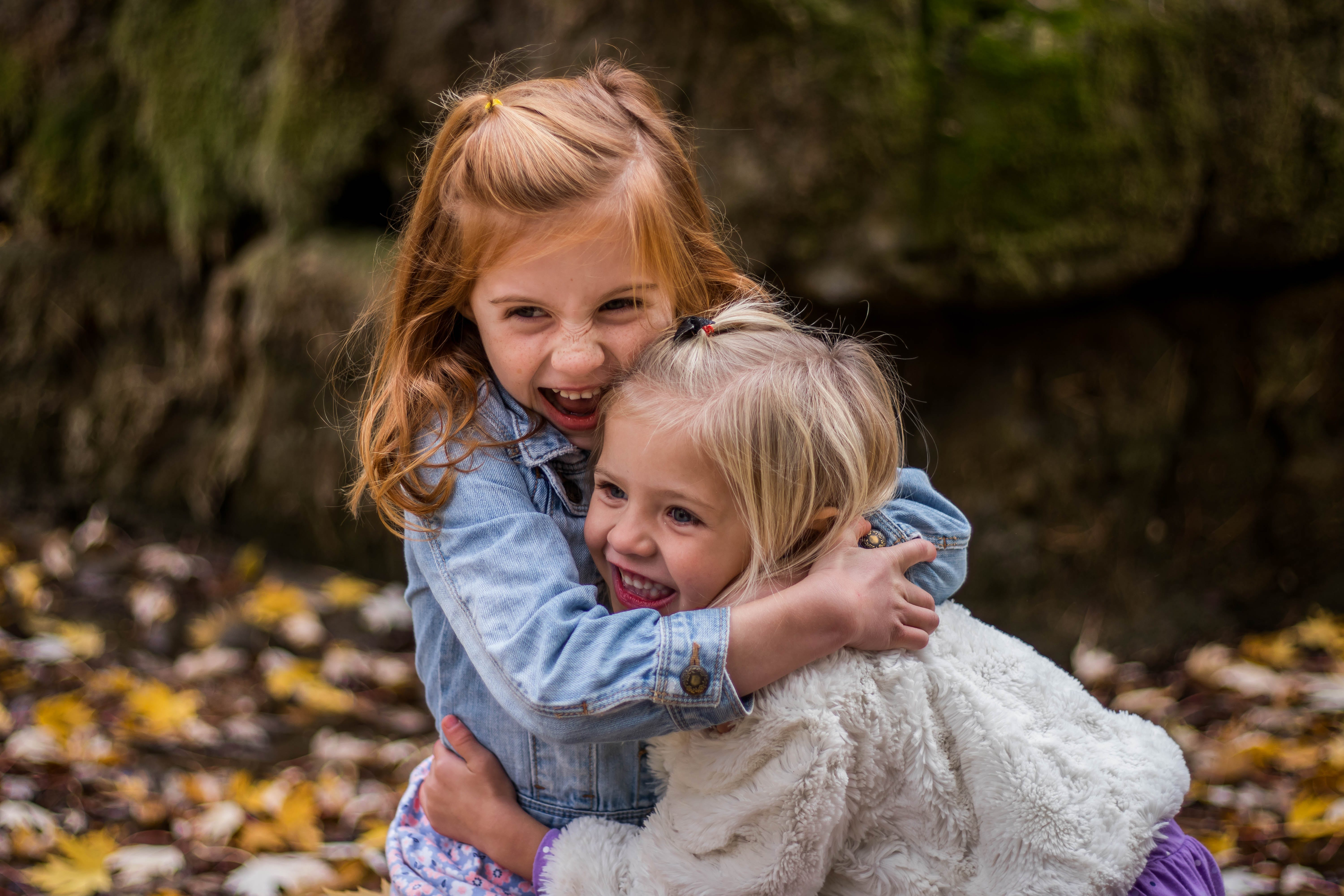 2 Girls Hugging Each Other Outdoor during Daytime