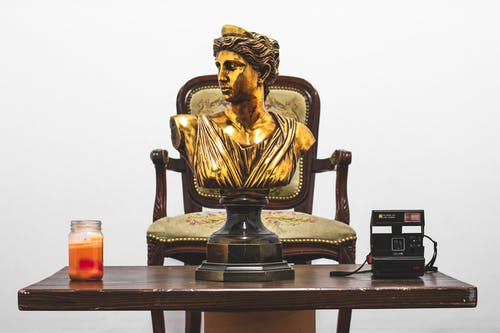 Gold Headbust on Table Near Camera and Votive Candle
