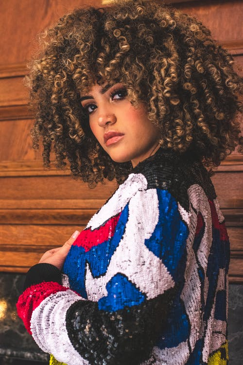 Side View Photo of Woman in Multicolored Sweater Posing