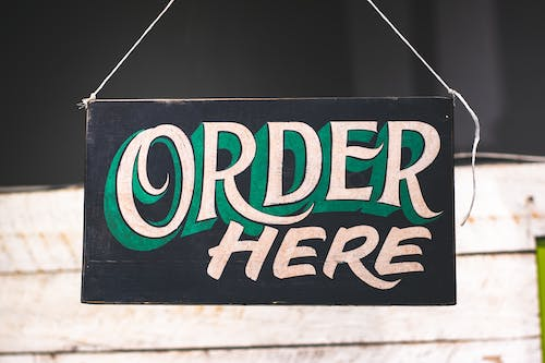 Order Here Text on Black Wooden Board