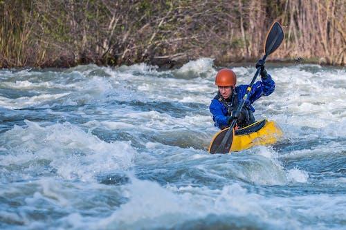 Photo of Man Paddling Kayak in Raging River
