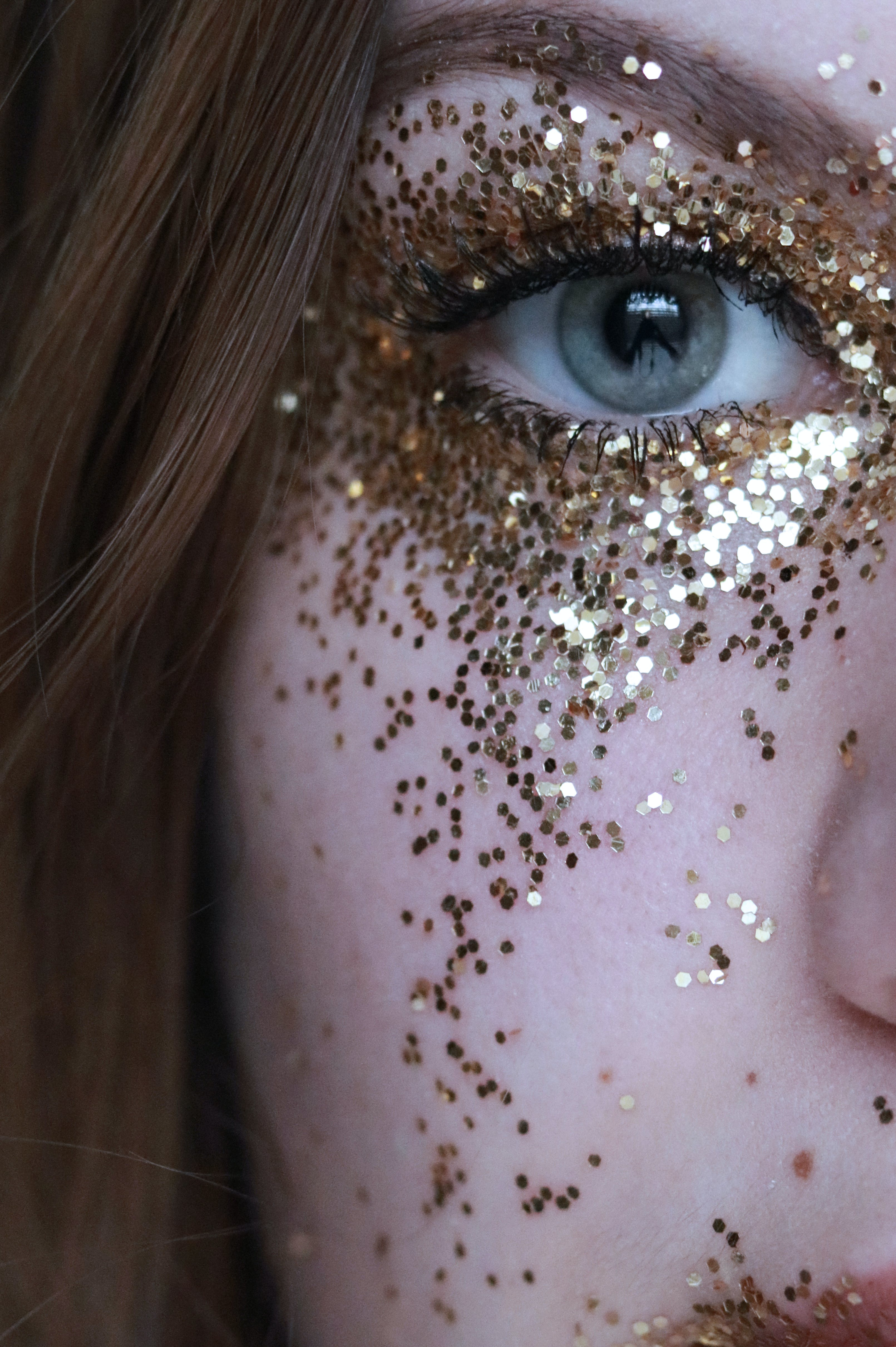 Close-Up Photo of Woman With Gold Glitters on Her Face