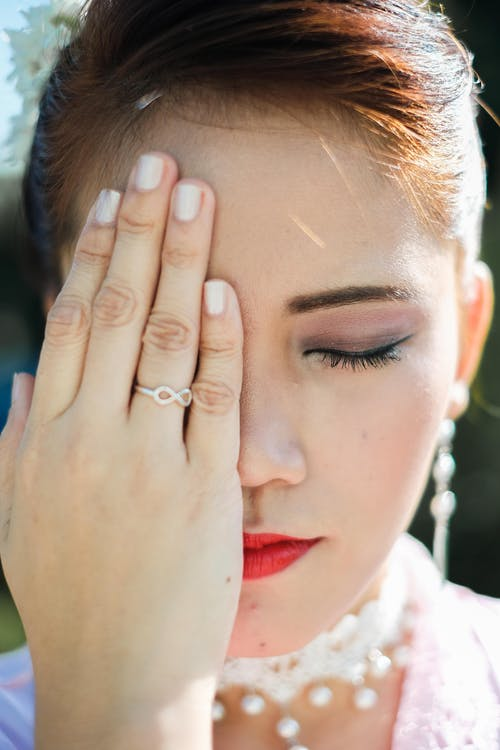 Woman Covering Her Right Eye With Her Right Hand