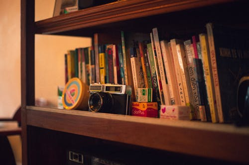 Black Vintage Camera on Bookshelf