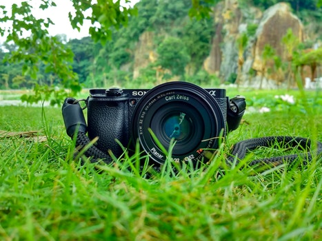 Black Sony Dslr Camera on Green Grass in Front of Brown and Green Mountain