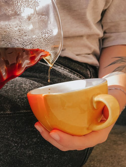 Close-up Photo of Person Pouring Coffee into Ceramic Mug