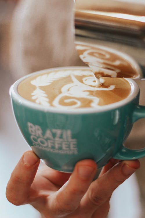 Person Holding Green Brazil Coffee Mug