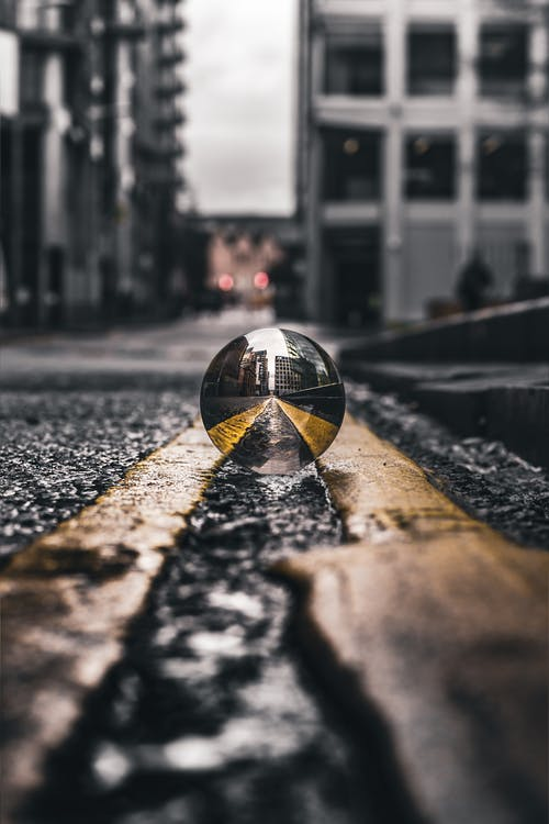 Selective Focus Photo of Lensball On Asphalt Road