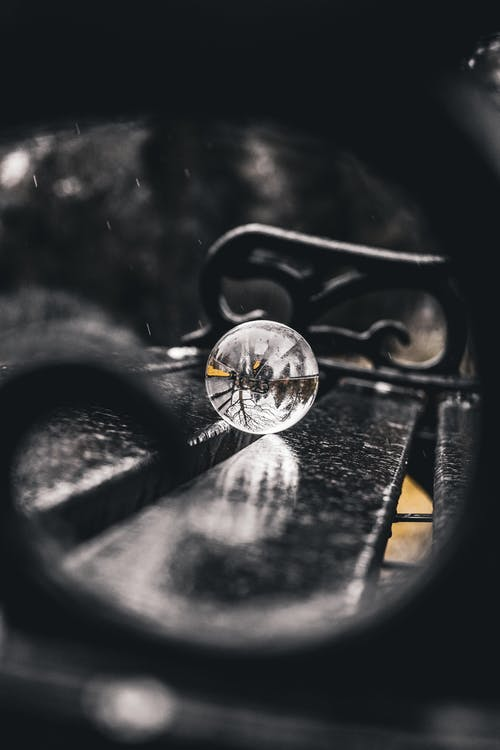 Selective Focus Photo of Lensball On Bench