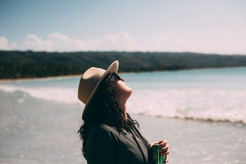 Woman Wearing Beige Hat Standing on Seashore Looking at Side