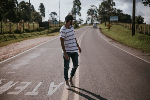 Photo of a Man Standing at Road