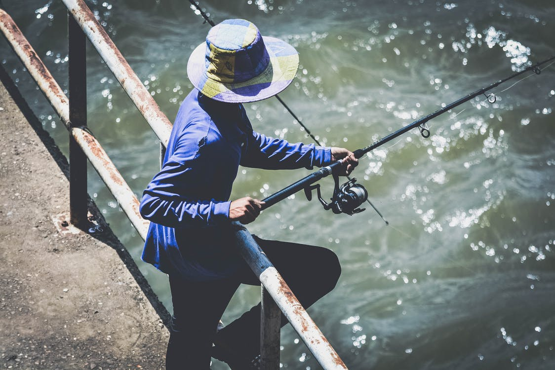 Person in Blue Long Sleeve Shirt and Black Pants Using Fishing Rod