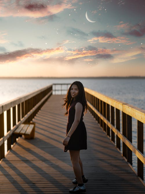 Woman Standing on Dock Wearing Black Dress