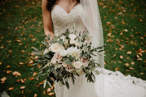 Woman Wearing White Wedding Dress With Bouquet Of Flowers