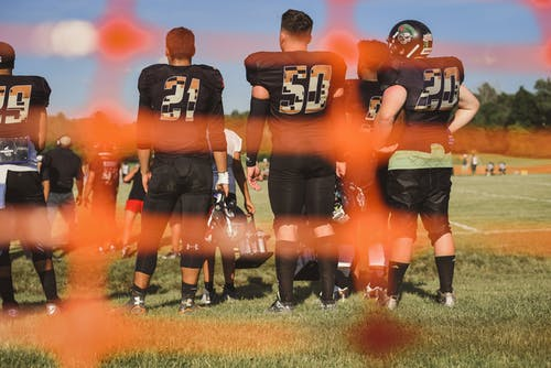 Selective Focus Photography Of Football Team On Field