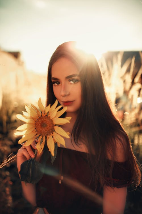 Woman Holding Sunflower in Close-up Photography