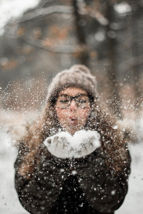 Woman Blowing Snow Outdoors