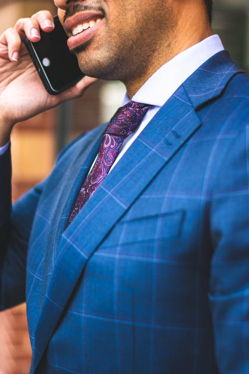 Close-up Photo of Man in Blue Pinstripe Suit Jacket Talking on The Phone